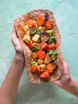 Stücke gebratenes hähnchen-curry-filet auf roggenfladenbrot mit gemüse. tortilla mit gemüse und gegrilltem fleisch in den händen