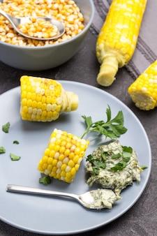 Stücke gekochter mais, soße und löffel auf grauem teller. maiskörner in schüssel. schwarzer hintergrund. ansicht von oben