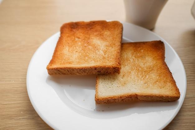 Stücke geröstetes geschnittenes brot auf einem weißen teller und kaffee auf holztisch, bereit, sandwich zum frühstück zu machen. selektiver fokus.