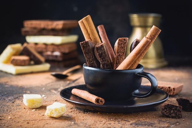 Stücke poröser schokolade und zimtstangen in schwarzer kaffeetasse auf dunkler alter oberfläche. selektiver fokus.