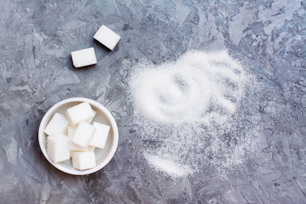 Stücke raffinierter zucker in einer schüssel und in einem stapel des zuckersands auf dem tisch