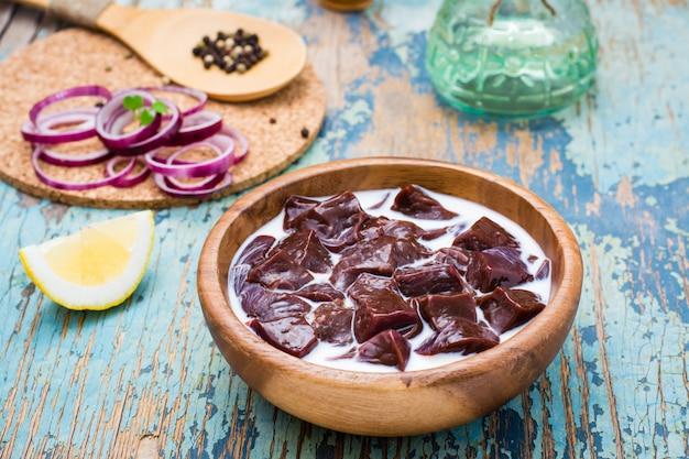 Stücke rohe rindfleischleber getränkt in milch in einer hölzernen schüssel und in bestandteilen für auf dem tisch kochen