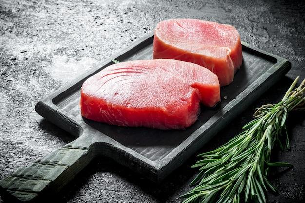 Stücke rohen thunfisch auf einem schneidebrett mit einem bündel rosmarin. auf schwarz rustikal