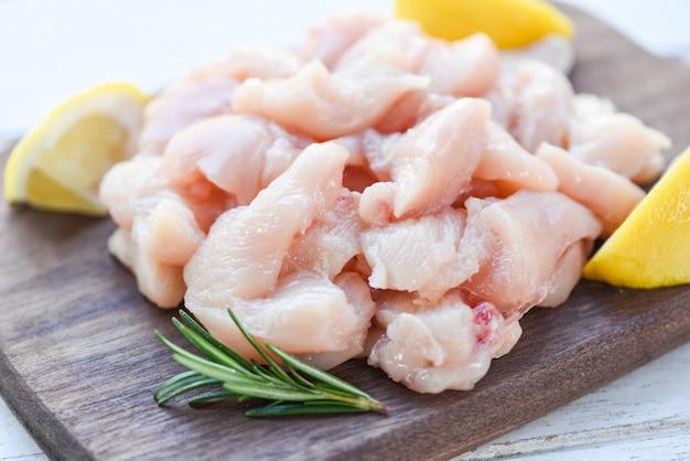 Stücke rohes hühnerfleisch mit rosmarin und zitrone / frische rohe schnitthühnerleiste auf hölzernem schneidebretthintergrund