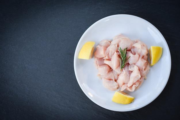 Stücke rohes hühnerfleisch mit rosmarin und zitrone / frische rohe schnitthühnerleiste auf weißem plattenhintergrund