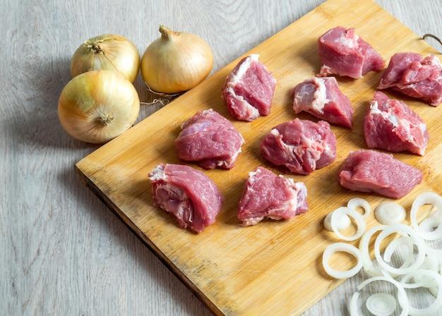 Stücke rohes rindfleisch und zwiebel auf schneidebrett