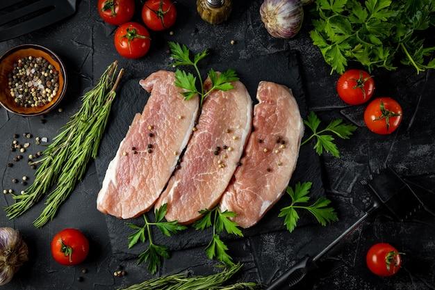 Stücke rohes schweinefleisch mit gewürzen für die zubereitung auf schwarz
