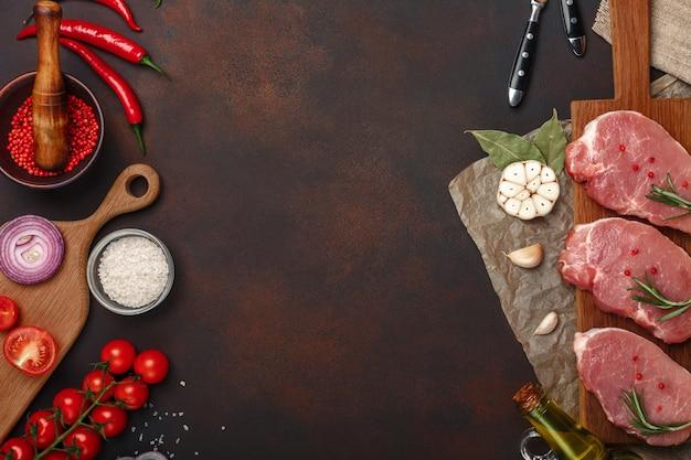 Stücke rohes schweinefleischsteak auf schneidebrett mit kirschtomaten, rosmarin, knoblauch, rotem pfeffer, lorbeerblatt, zwiebel, salz und gewürzmörtel auf rostigem braunem hintergrund