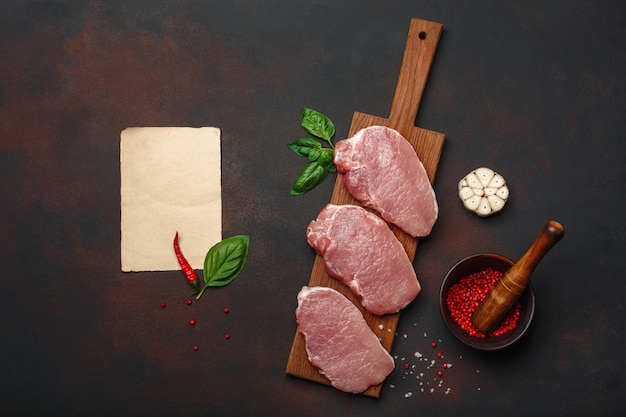 Stücke rohes schweinefleischsteak mit basilikum, knoblauch, pfeffer, salz- und gewürzmörtel und blatt papier auf schneidebrett