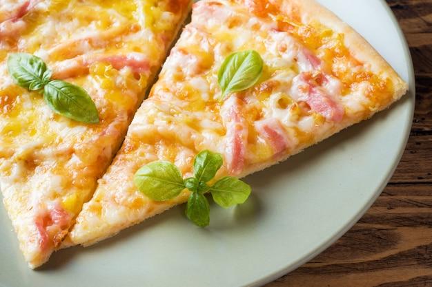 Stücke selbst gemachte pizza auf einer platte auf einem holztisch.