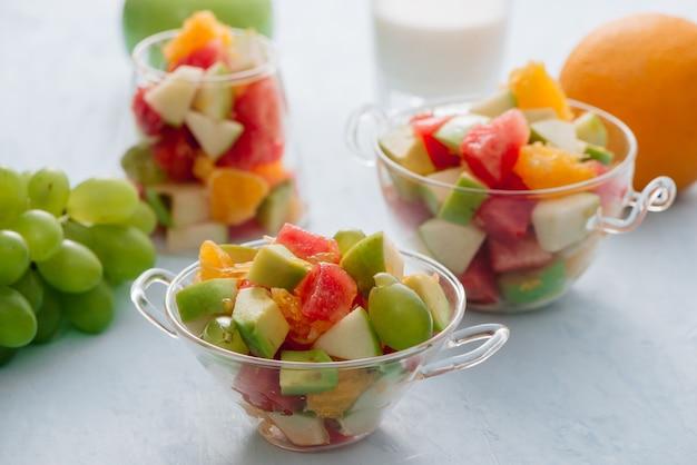 Stücke tropischer früchte in einem glas. geschnittene orange, apfel, scheiben wassermelone in glasschüssel. zitrusfrüchte