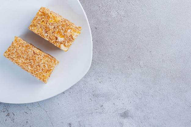 Stücke türkischer köstlichkeiten beschichtet mit besprühten süßigkeiten auf einer weißen platte auf marmorhintergrund.