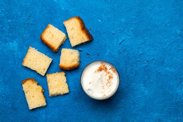 Stücke vanillekuchen und ein glas cappuccino auf einem klassischen blauen hintergrund