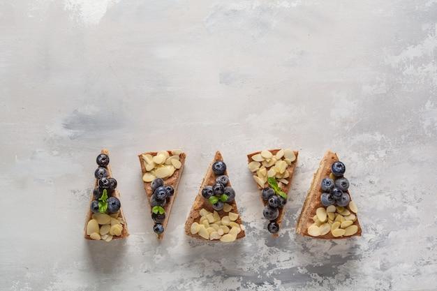 Stücke veganen rohen schokoladenkäsekuchens mit blaubeeren und mandeln. gesundes veganes lebensmittelkonzept, lebensmittelhintergrund, kopienraum, draufsicht.