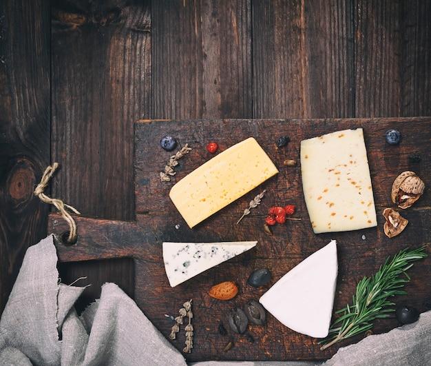 Stücke verschiedene käse auf braunem hölzernem brett: brie, roquefort, käse mit nüssen