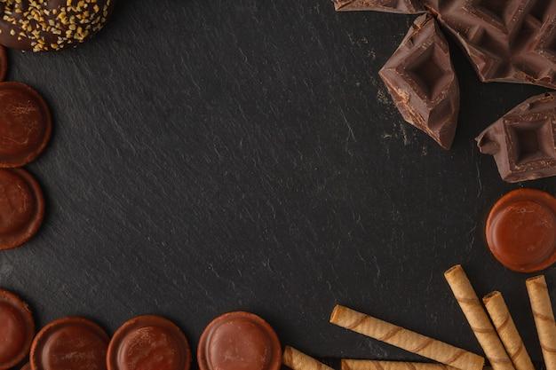 Stücke von bittersüßer dunkler schokolade breiteten sich auf einem hölzernen hintergrund aus