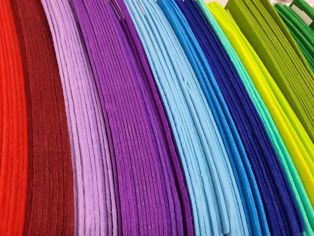 Stücke von bunten textilmustern aus filz in verschiedenen farben zum nähen im bastelladen heimwerken und basteln...