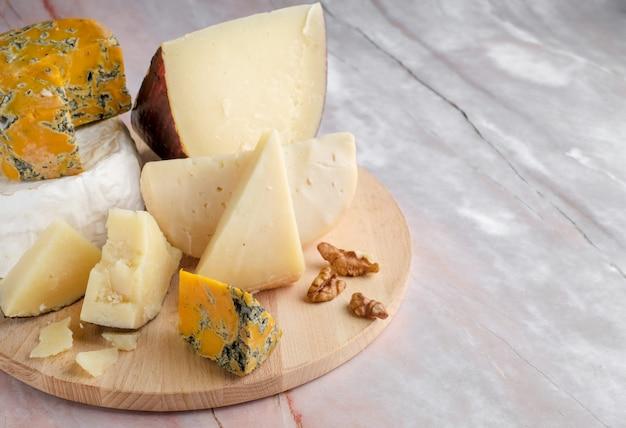 Stücke von camembert, parmesan und shropshire-blauschimmelkäse auf einem holzteller
