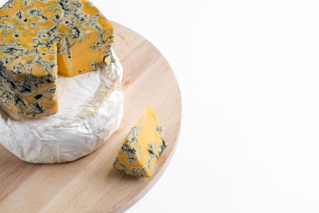 Stücke von camembert und shropshire blauschimmelkäse auf einem holzteller