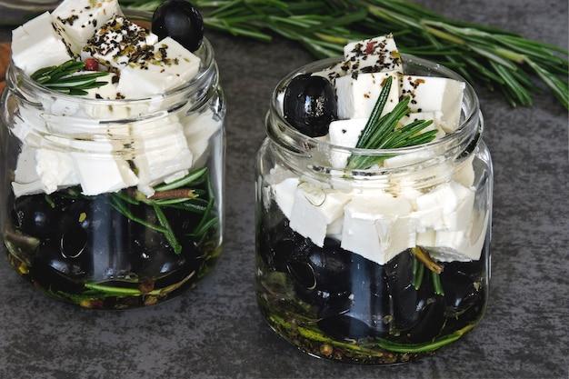 Stücke von feta und oliven in gläsern mit rosmarin und gewürzen. keto-snack