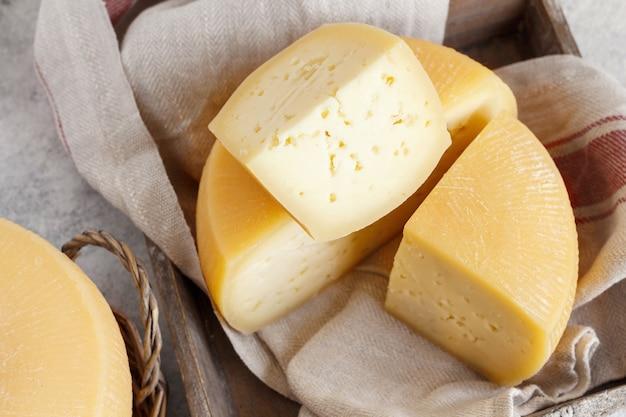 Stücke von frischem hausgemachtem italienischem käse auf einem tablett schließen oben
