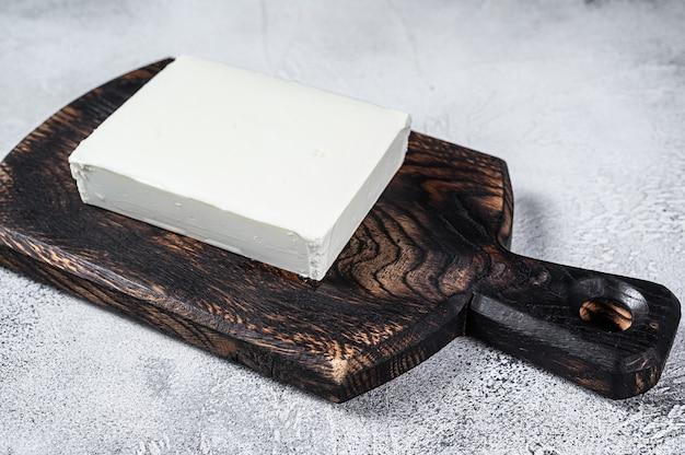 Stücke von frischem paneer-käse auf einem schneidebrett.