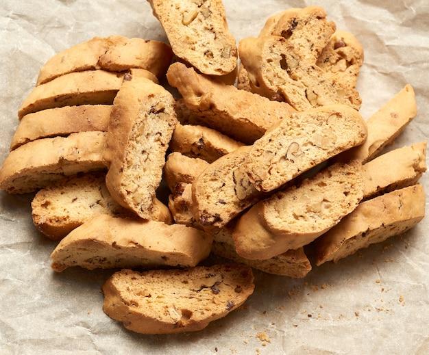 Stücke von gebackenen italienischen weihnachtsbiscotti-keksen auf einem braunen zerknitterten papier