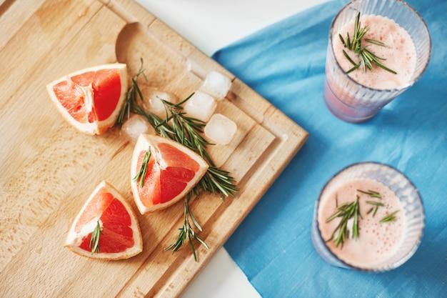 Stücke von grapefruit und rosmarin auf holzschreibtisch. gesunde detox-diät smoothie.fitness gewichtsverlust konzept. von oben.