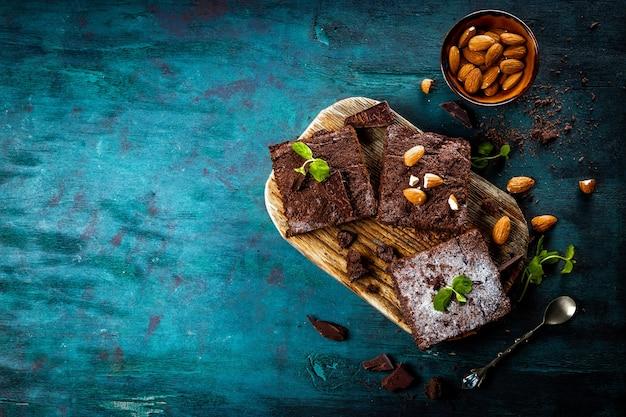 Stücke von hausgemachtem schokoladen-brownie mit minzblättern und nüssen auf dem blauen hölzernen hintergrund, oben