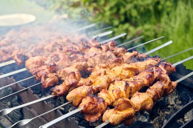 Stücke von köstlichem gegrilltem fleisch am spieß, der auf heißen kohlen kocht. gebratenes schweinefleisch auf dem grill zubereitet. grillparty in der natur. ansicht von oben hautnah.