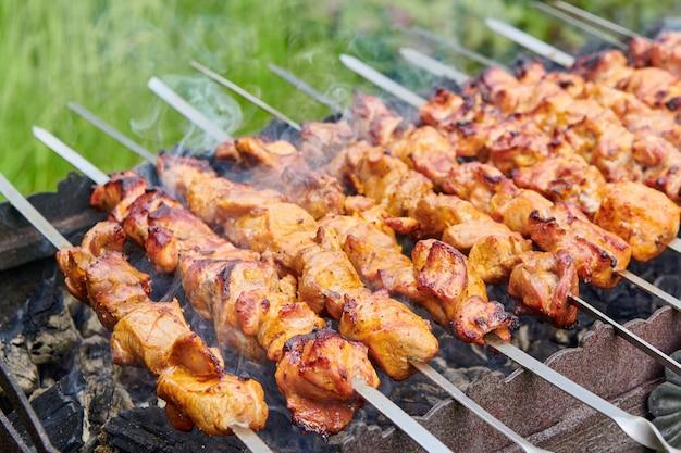 Stücke von köstlichem gegrilltem fleisch am spieß, der auf heißen kohlen kocht. gebratenes schweinefleisch auf dem grill zubereitet. grillparty in der natur. nahaufnahme.