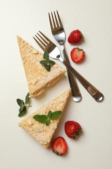 Stücke von napoleon-kuchen, erdbeere und gabeln auf weißer oberfläche