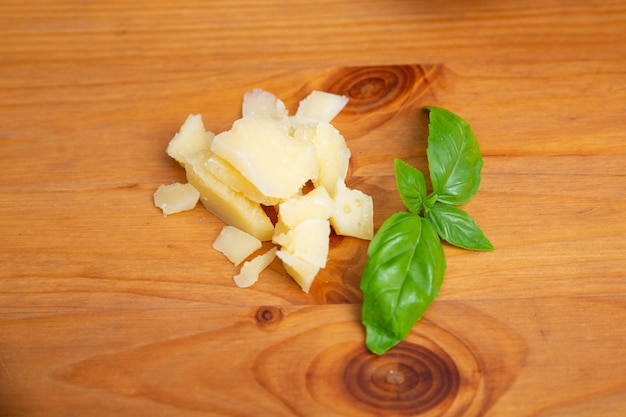 Stücke von parmesan und grünem basilikum auf holztisch