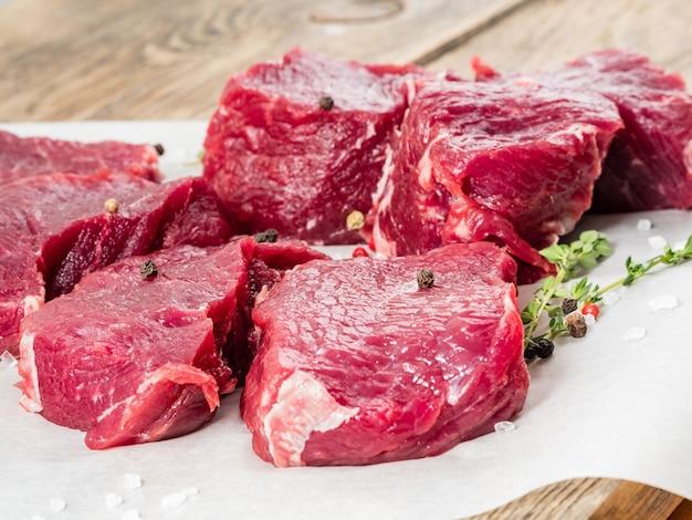 Stücke von rohem striploin. rohes rindfleisch mit gewürzen auf pergamentpapier auf hölzernem hintergrund