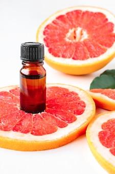 Stücke von roter grapefruit und öl in einer flasche auf weißem hintergrund