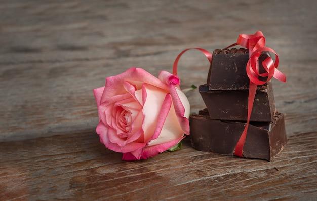 Stücke von schokolade und blume auf dem hölzernen hintergrund. drei schokoladenstücke mit rotem band und rose auf dunkler holzoberfläche