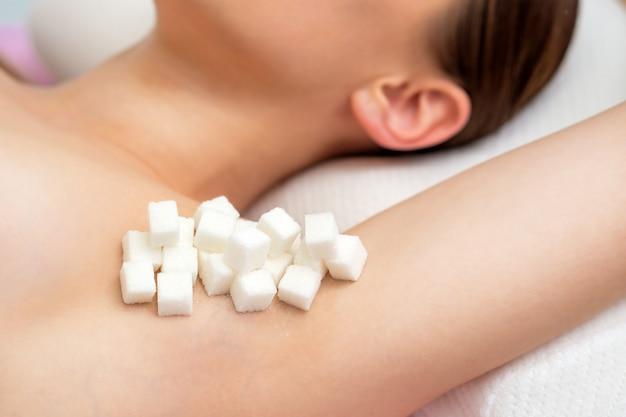 Stücke weißen zuckers auf der achsel einer frau.
