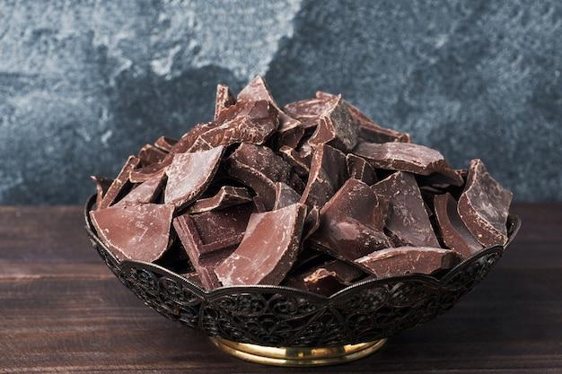 Stücke zerquetschte dunkle schokolade in einer platte auf einer dunklen oberfläche.