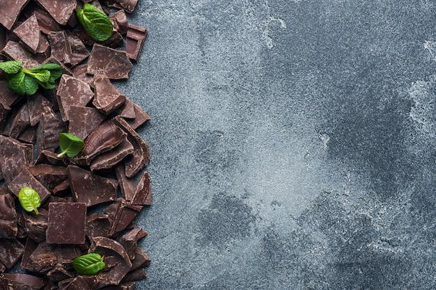 Stücke zerquetschte dunkle schokolade mit dunklem strukturiertem hintergrund der tadellosen blätter
