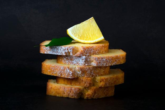 Stücke zitrus-pfund-kuchen mit zuckerpulver und zitronenscheibe