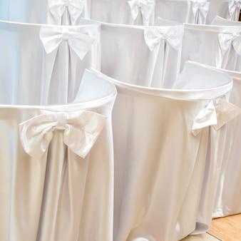 Stühle bedeckt mit weißem stoff auf hochzeitszeremonie in den reihen