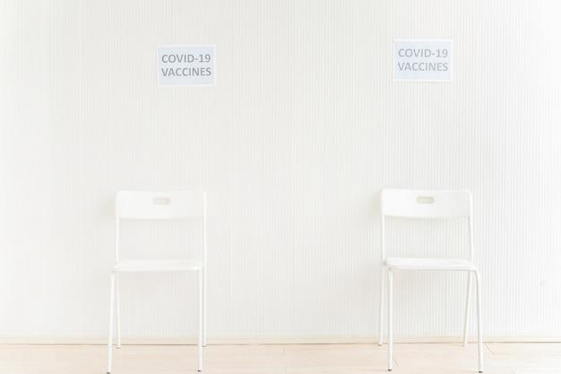 Stühle in wartestation platziert, um covid-impfstoff in klinik oder krankenhaus mit weißer wand zu bekommen