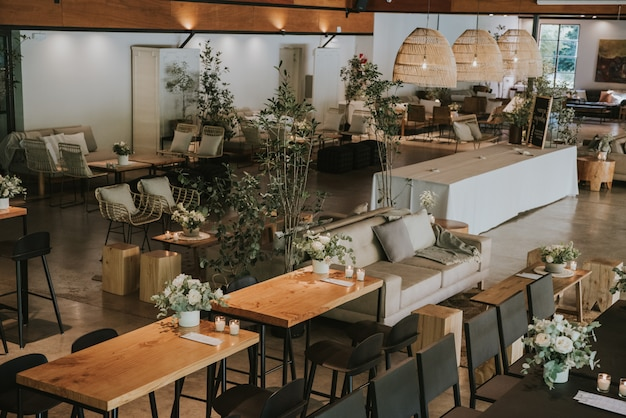 Stühle und sessel mit holztischen, dekoriert mit weißen pflanzen und blumen