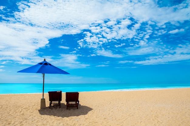 Stühle und sonnenschirme auf einem schönen strand und einem blauen himmel