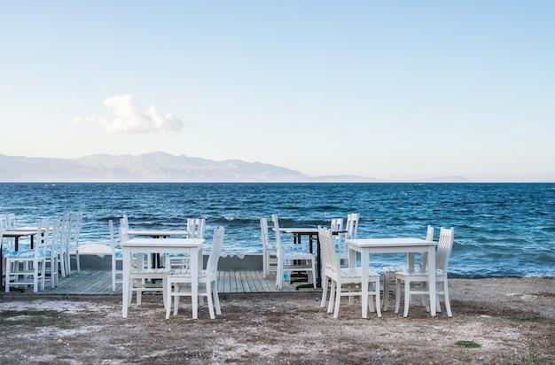 Stühle und tabellen im alten café nahe dem meer, ciftlikkoy-fischerdorf, ägäische region, die türkei