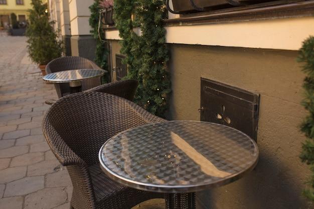 Stühle und tisch in der nähe des weihnachtlich dekorierten restaurants