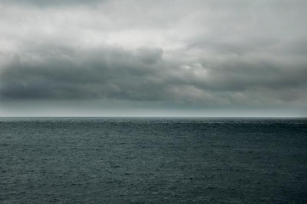 Stürmische wolken oder regenwolken über einem dunklen meer