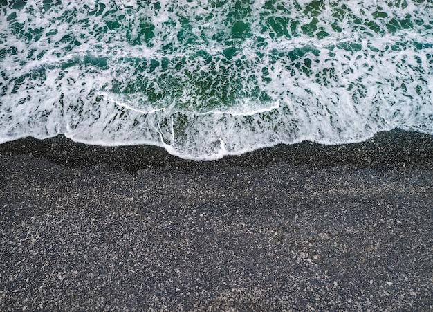 Stürmisches wetter, meereswellen, die an einem ufer mit vulkanischem schwarzem sand brechen, hintergrund mit kopierraum