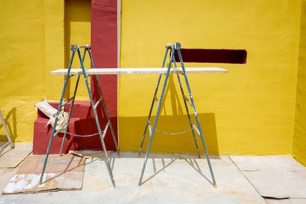 Stützen und gerüste mit holzbrettern, die von einem maler verwendet werden, um eine wand zu streichen.