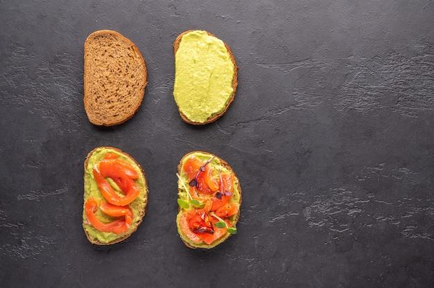 Stufen der herstellung eines sandwichs aus brot, guacamole, gesalzenem lachs, gebackenen tomaten und gemüse